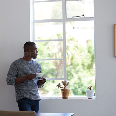 Buy stock photo Shot of a young businessman having a coffee break and looking out the window in a modern office