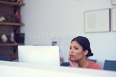 Buy stock photo Shot of a young businesswoman looking serious while using a computer in a modern office
