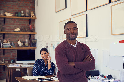 Buy stock photo Portrait of a confident young businessman working in a modern office with his colleague in the background