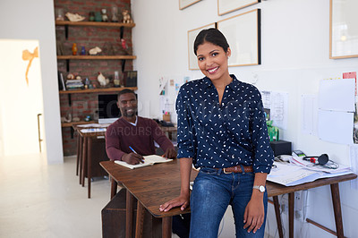 Buy stock photo Portrait of a confident young businesswoman working in a modern office with her colleague in the background