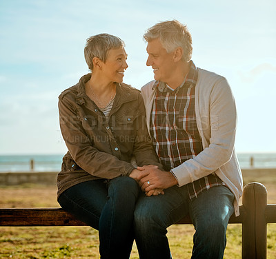 Buy stock photo Cropped shot of an affectionate senior couple sitting on a wooden railing at the beach