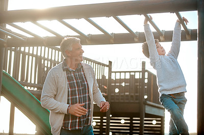 Buy stock photo Cropped shot of an adorable little boy playing on an outdoor jungle gym with his grandfather