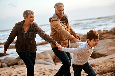Buy stock photo Cropped shot of an adorable little boy leading his grandparents by the hand on the beach