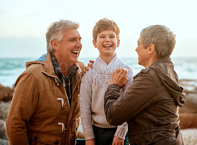Buy stock photo Cropped shot of an adorable little boy and his grandparents laughing at the beach
