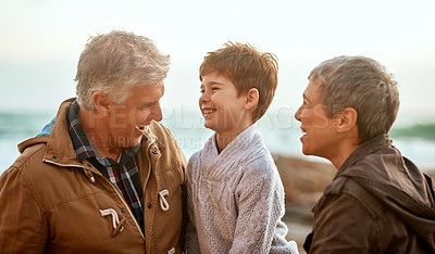 Buy stock photo Cropped shot of an adorable little boy and his grandparents at the beach