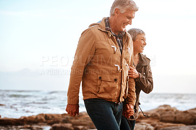 Buy stock photo Cropped shot of an affectionate senior couple walking hand in hand on the beach