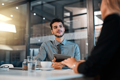 Buy stock photo Shot of a young businessman having a discussion with a colleague in an office