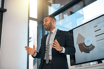Buy stock photo Shot of a young businessman presenting data on a screen during a meeting in an office
