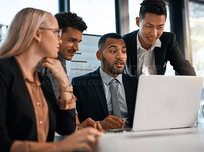 Buy stock photo Shot of a group of businesspeople using a laptop together in an office