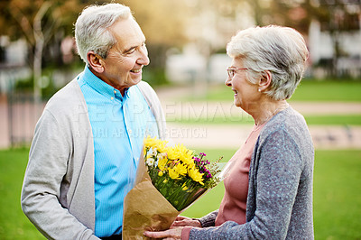Buy stock photo Shot of a senior man surprising his wife with flowers at the park