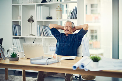 Buy stock photo Cropped shot of a senior businessman sitting with his hands behind his head while working from home
