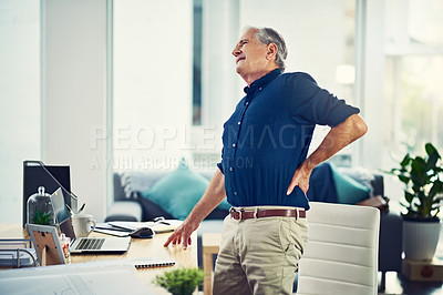 Buy stock photo Cropped shot of a senior businessman experiencing body pain while working from home