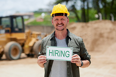 Buy stock photo Cropped portrait of a handsome mature construction worker holding a hiring sign while standing on a construction site