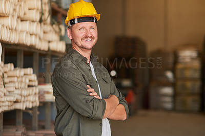 Buy stock photo Cropped portrait of a handsome mature construction worker standing with his arms folded in an industrial warehouse