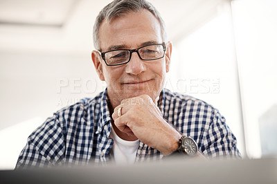 Buy stock photo Shot of a mature man working on a laptop at home
