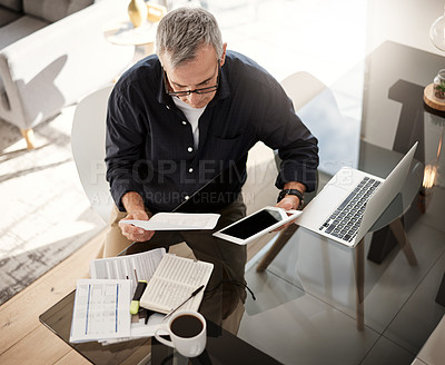 Buy stock photo High angle shot of a mature man using a digital tablet while going through some paperwork at home