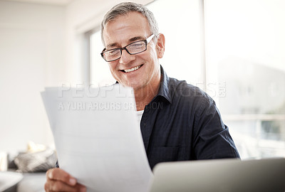 Buy stock photo Shot of a mature man going through some paperwork at home