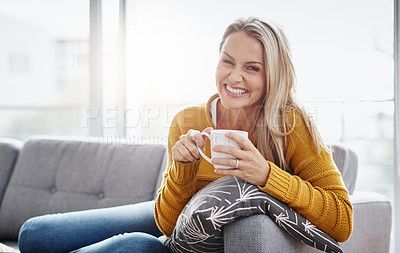 Buy stock photo Portrait of an attractive mature woman enjoying a beverage while relaxing on the sofa at home