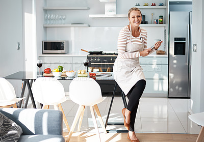 Buy stock photo Shot of a mature woman using her digital tablet while wearing her apron in the kitchen