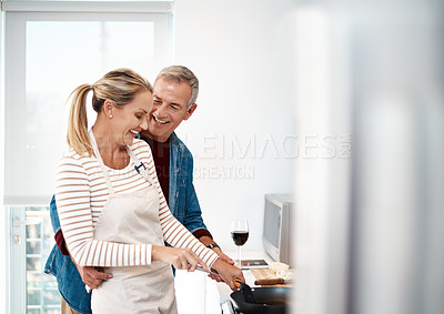 Buy stock photo Shot of a man standing behind his wife while she prepares a meal