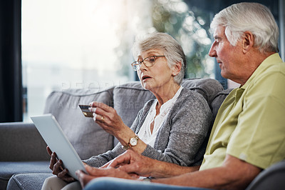 Buy stock photo Shot of a senior couple using a digital tablet and credit card on the sofa at home