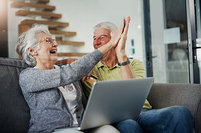Buy stock photo Shot of a senior couple using a laptop and credit card on the sofa at home