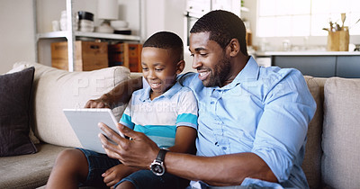 Buy stock photo Cropped shot of a young father using a tablet with his adorable little son at home