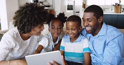 Buy stock photo Cropped shot of a young family using a tablet together while chilling on the sofa at home