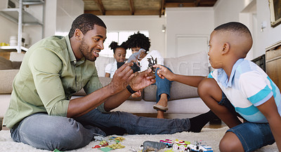 Buy stock photo Shot of a father and son playing with toys together while the mother is using a tablet with her  daughter on the sofa at home
