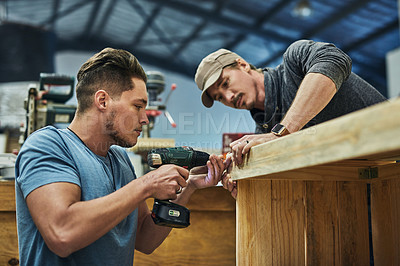 Buy stock photo Cropped shot of two carpenters putting together a wood piece in a workshop