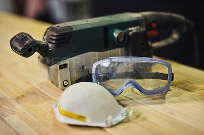 Buy stock photo Shot of protective workwear and a sander on a table