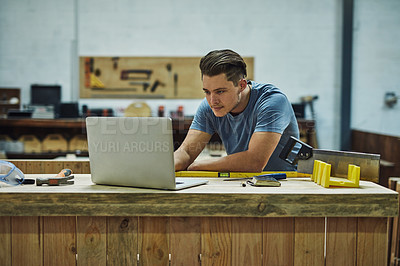 Buy stock photo Cropped shot of a carpenter using a laptop in his workshop