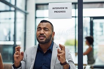 Buy stock photo Cropped shot of a handsome young businessman sitting outside the boardroom with his fingers crossed