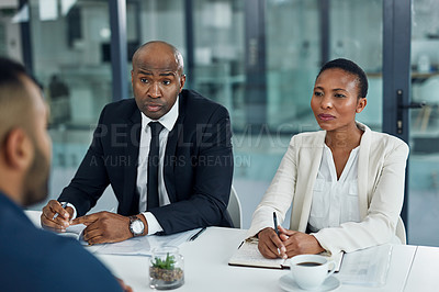 Buy stock photo Cropped shot of two mature businesspeople interviewing a male candidate in the boardroom