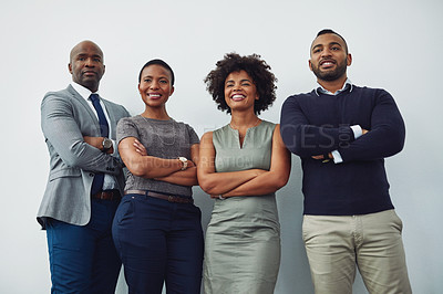 Buy stock photo Cropped shot of a group of businesspeople standing with their arms folded in their corporate office