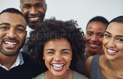 Buy stock photo Cropped portrait of a group of businesspeople looking happy while standing in their corporate office