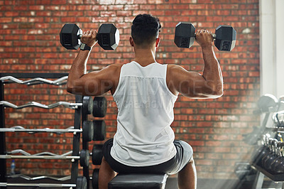 Buy stock photo Rearview shot of a young man working out with weights in a gym