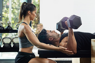 Buy stock photo Shot of a young man lifting weights with his girlfriend assisting him