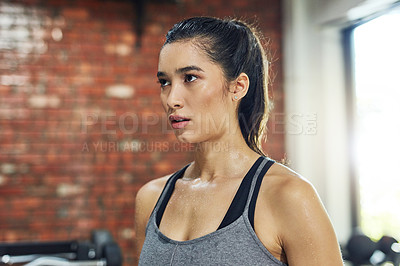 Buy stock photo Shot of young woman working out in a gym