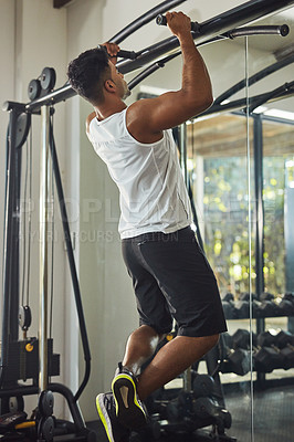 Buy stock photo Shot of a young man doing pull ups in a gym