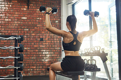 Buy stock photo Rearview shot of a young woman working out with weights in a gym
