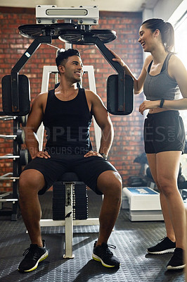 Buy stock photo Shot of a young couple chatting during their workout in a gym