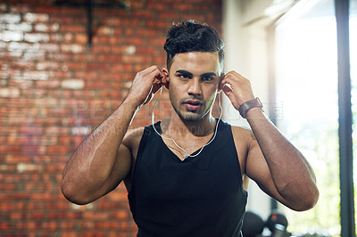 Buy stock photo Portrait of a young man putting on earphones in a gym