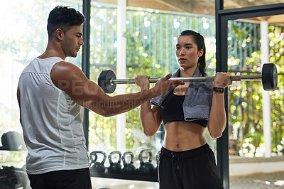 Buy stock photo Shot of a young woman lifting weights with her boyfriend assisting her