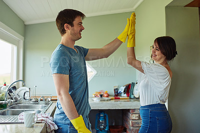 Buy stock photo Shot of a young couple high fiving while doing chores together at home