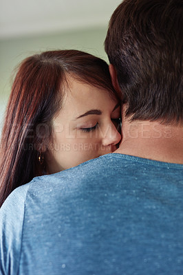 Buy stock photo Shot of a young woman hugging her boyfriend at home