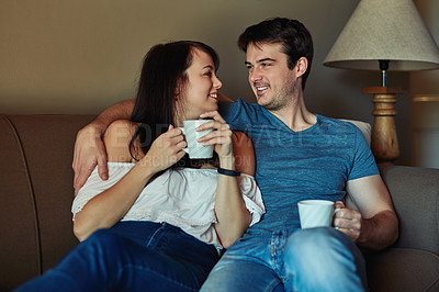 Buy stock photo Shot of a young couple drinking coffee while relaxing together at home