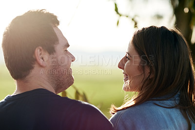 Buy stock photo Shot of a happy young couple sharing a romantic moment in the park