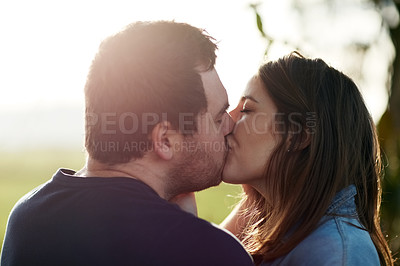 Buy stock photo Shot of a happy young couple kissing in the park