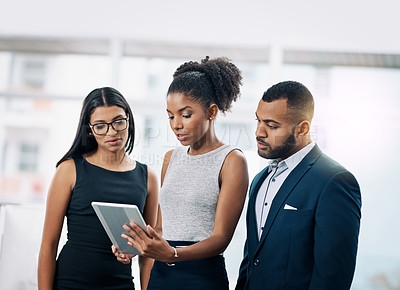 Buy stock photo Shot of a business team using a digital tablet while having an informal meeting